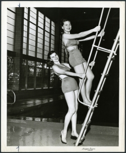 Rice Institute women students climbing the diving board ladder at the gym pool