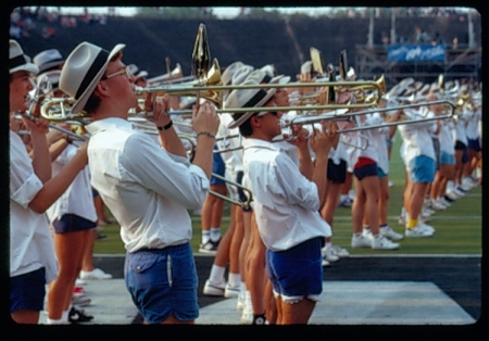 MOB members playing trombones in shorts at football game, 2000