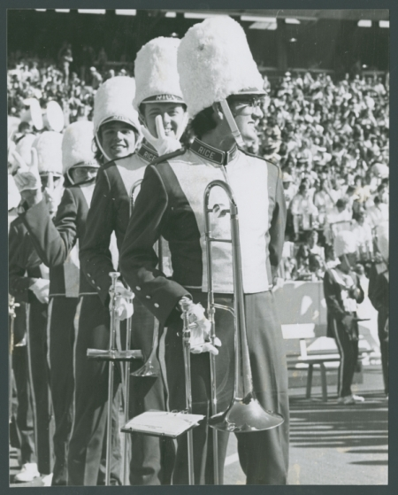 MOB horn section lined up at Rice University football game with stadium crowd in background
