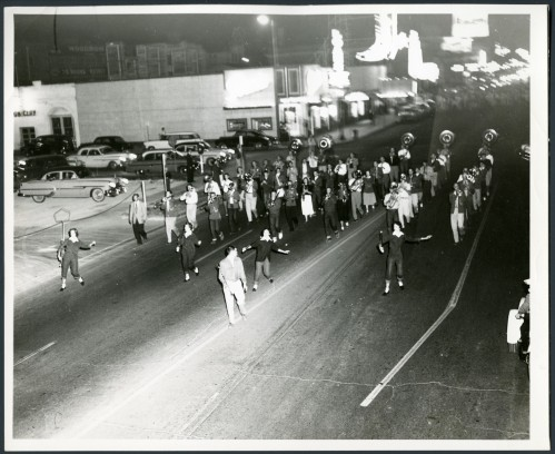 Band marching at night, 1950s