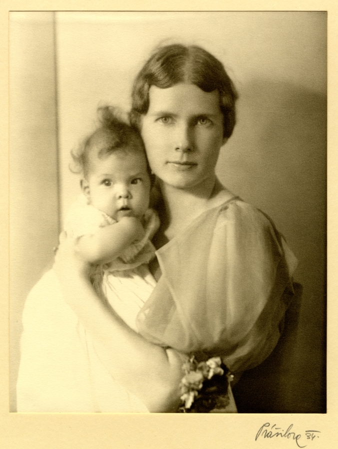 Black and white photograph of Marie Lee Phelps, seated, wearing a light dress and holding child, 1936