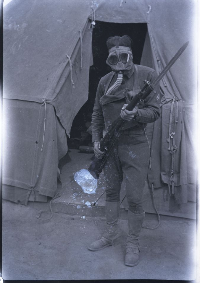 Image of Paul B. Hendrickson wearing a gas mask and holding a rifle with a bayonet.