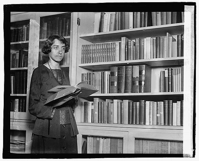 Elizabeth Kalb in the literature and library department of the National Woman's Party in its Washington, D.C. headquarters. She is holding a book standing next to book shelving.
