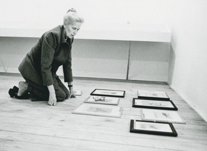 Dominique de Menil kneeling on the floor organizing Max Ernst paintings for an exhibit.