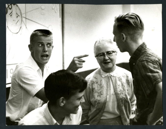 During a drama class at the Rice Summer School for High School Students, three students are role-playing while a teacher watches. One of the students is gesturing aggressively at another student. In the background can be seen a whiteboard with diagrams drawn on it. Original resource is a black and white photograph.