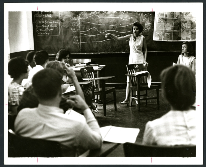 A classroom during the Rice Summer School for High School Students session. The students are seated in a semi-circle, listening to the professor as she lectures at the front of the room. The professor is standing behind her chair, one hand on the back. Behind her is a blackboard covered with notes about economics and foreign aid. A large map is attached to one side of the blackboard, showing Europe and the Mediterranean, along with additional inset maps. Original resource is a black and white photograph.