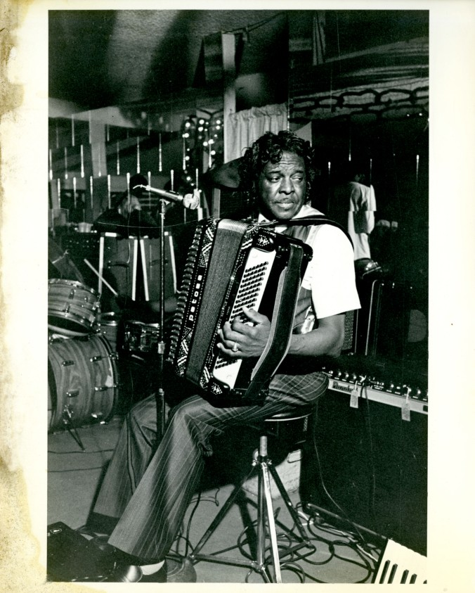 Black and white image of Clifton Chenier on a stage holding an accordion on his lap.