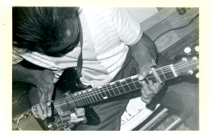 Black and white image of unknown bass player, shot at an unusual angle