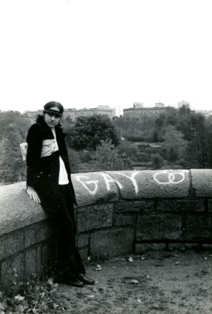 "Black and white image of Joseph Lomax next to the spray painted word ""Gay."""