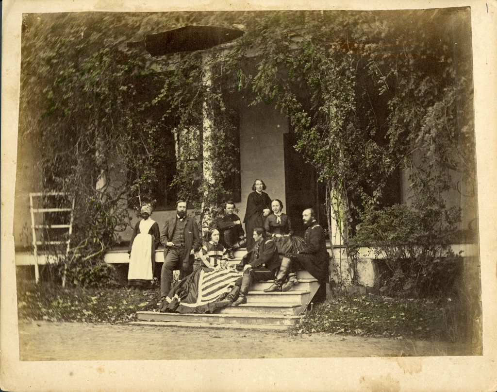 Family sitting with soldiers in front of a house. Woman slave to the left.