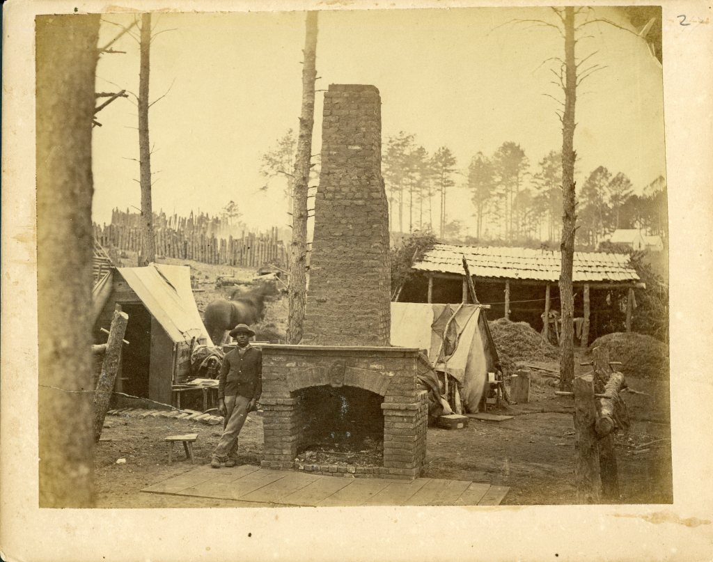 Black man standing by the remnants of a chimney.