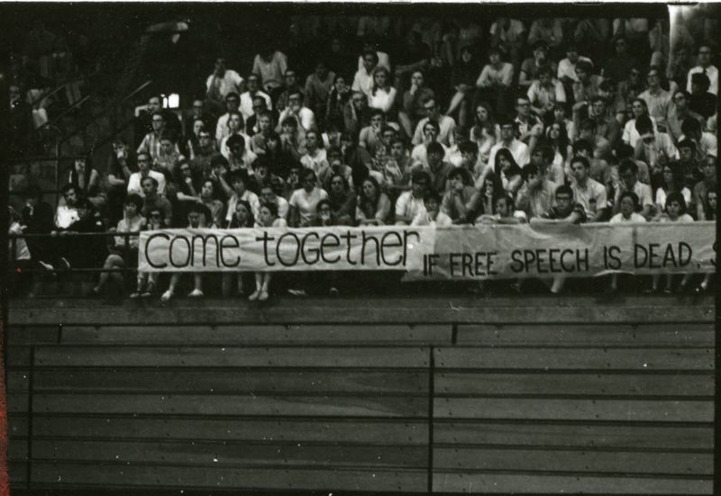 """Students gathered, sitting in bleachers with the signs """"come together"""" and """"if free speech is dead..."""""""