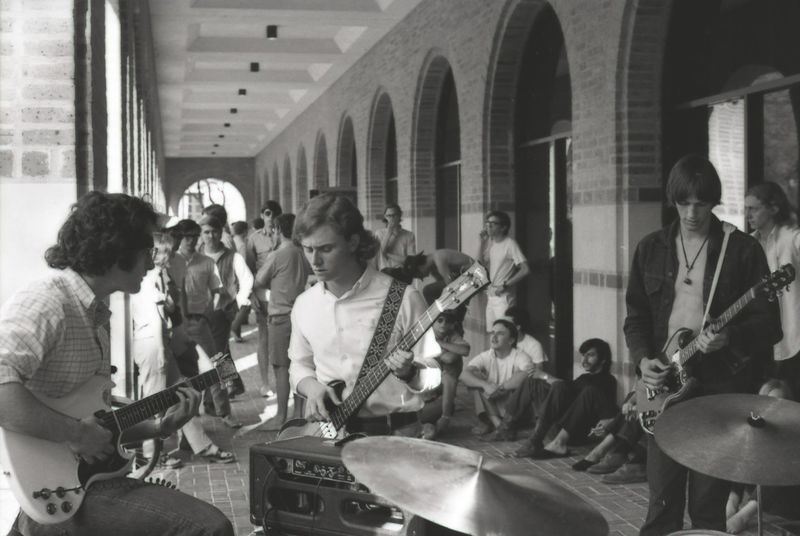 Image of four piece band playing at Allen Center with others sitting down and standing around.