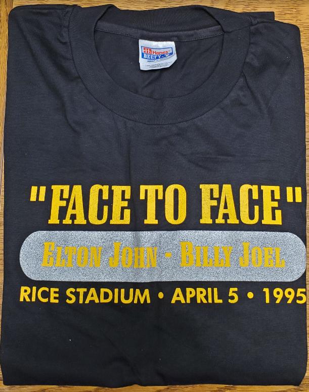 Black t-shirt. Caption reads: Face to Face Elton John Billy Joel Rice Stadium April 5 1995