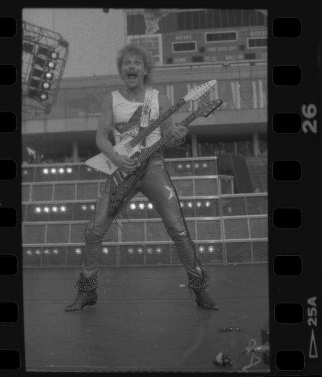 Guitarist holding double neck guitar.