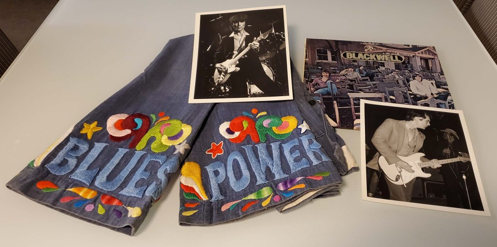 """Image of embroidered bell bottom jeans that say """"BLUES POWER,"""" an LP, and two photographs of Jimmy Don Smith"""