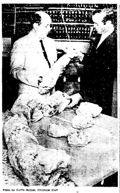 Black and white microform image of Manuel Armando Yramategui holding a fossilized bone next to his colleague.